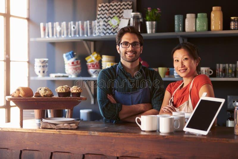 Portrait de café courant de couples derrière le compteur photo stock
