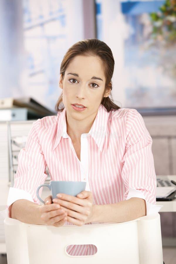 Jeune femme en café potable de bureau image stock
