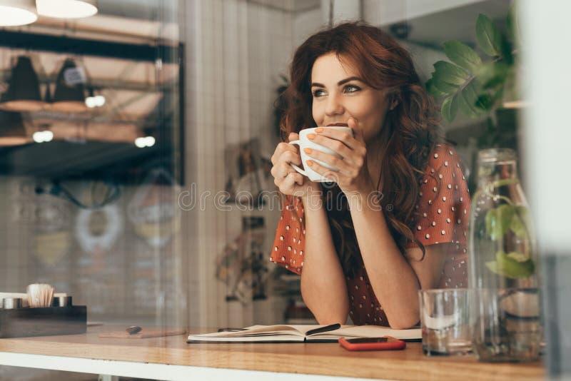 portrait de café potable de jeune femme à la table avec le carnet image stock
