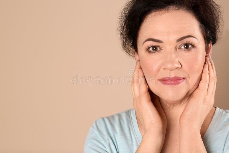 Portrait de charmer la femme mûre avec la belle peau saine de visage et le maquillage naturel sur le fond beige, plan rapproché image stock