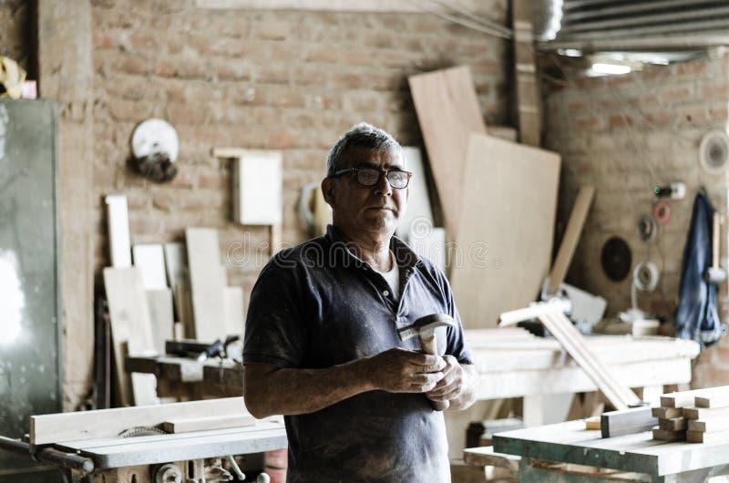Portrait de charpentier supérieur dans son atelier et de regarder la caméra photos stock