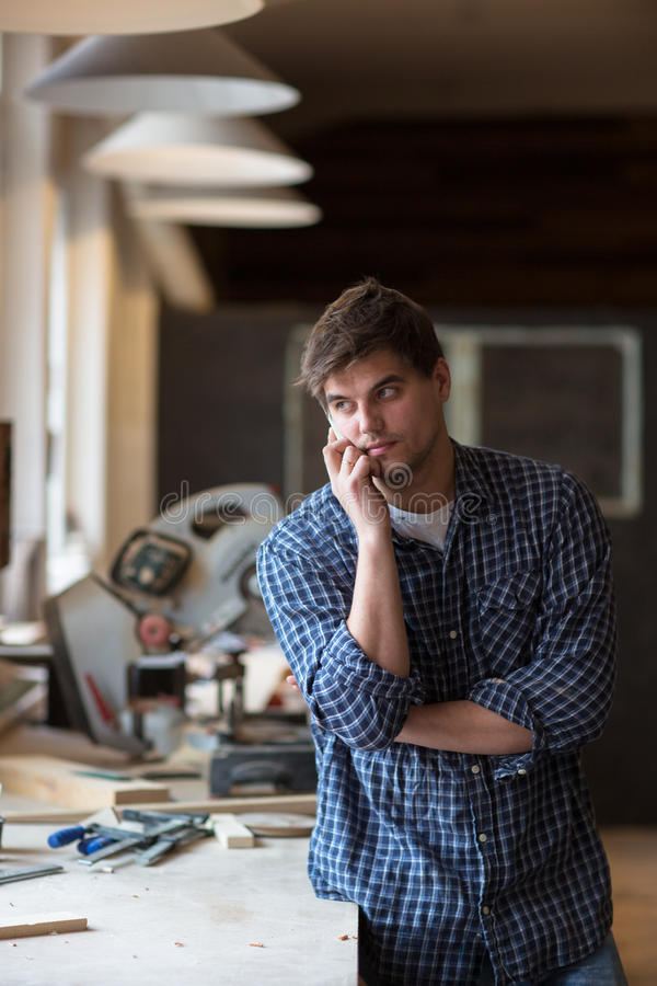 Portrait de charpentier supérieur travaillant à son atelier tandis que séjour photo libre de droits