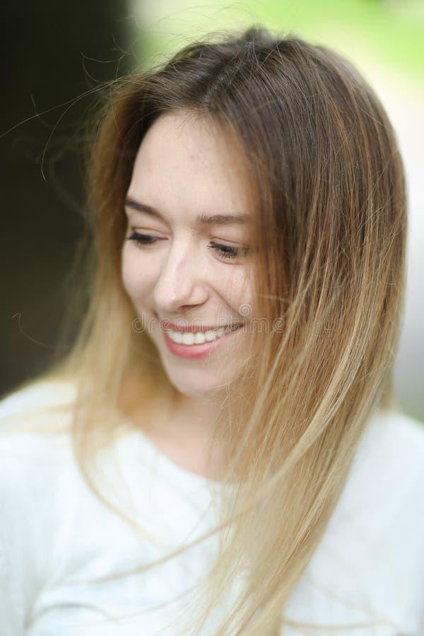 Portrait de chemisier blanc de port de jeune femme heureuse dehors images stock