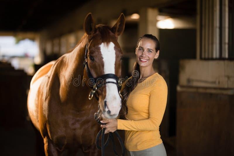 Portrait de cheval se tenant prêt de sourire de jockey féminin photographie stock