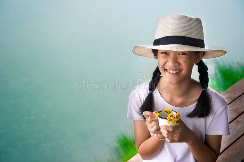 Portrait de cheveux de tresse de fille d'enfant de l'Asie 11s long avec le chapeau blanc avec le fond de lac de l'eau bleue d'été images stock