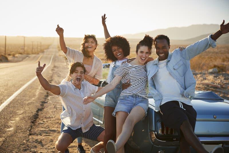 Portrait de cinq amis se tenant prêt la voiture classique convertible sur le voyage par la route photographie stock