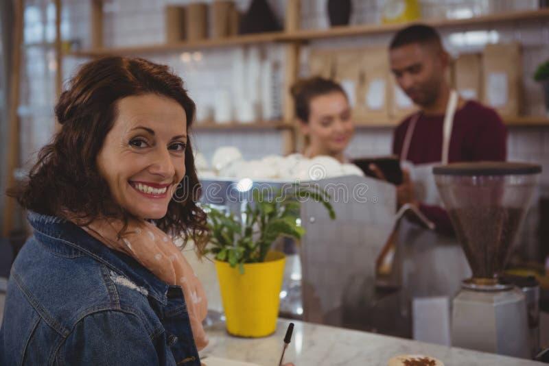 Portrait de client avec des propriétaires discutant en café photos stock