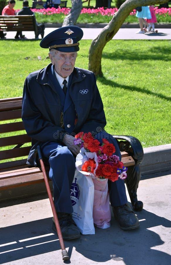 Portrait de combattant, il assied sur un banc et tient des fleurs photo stock