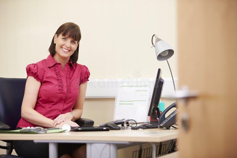Portrait de conseiller féminin Working At Desk dans le bureau photos stock