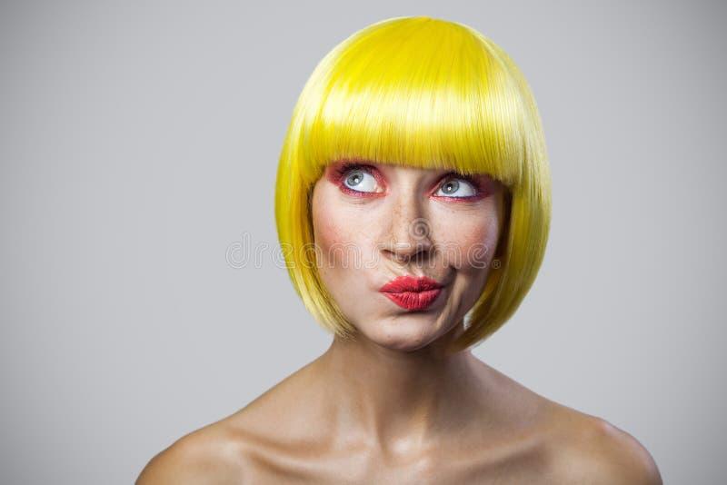Portrait de considérer la jeune femme mignonne avec des taches de rousseur, le maquillage rouge et la perruque jaune regardant lo photos libres de droits