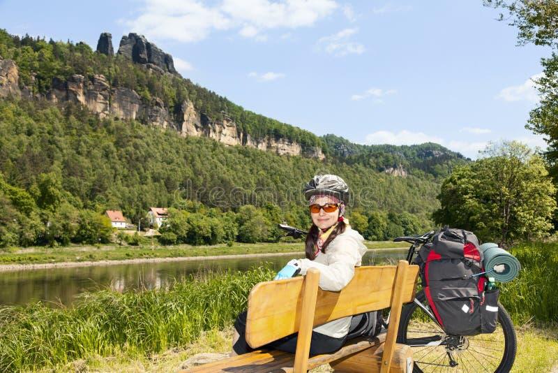 Portrait de cycliste de femme se reposant sur un banc en nature photos stock