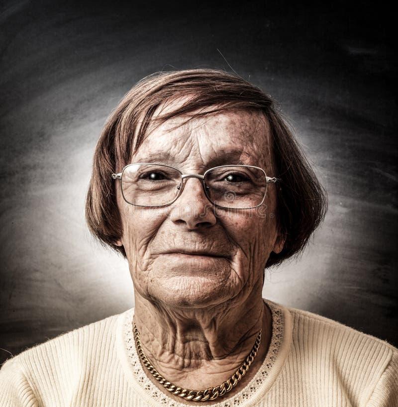 Portrait de dame âgée à l'arrière-plan foncé images stock