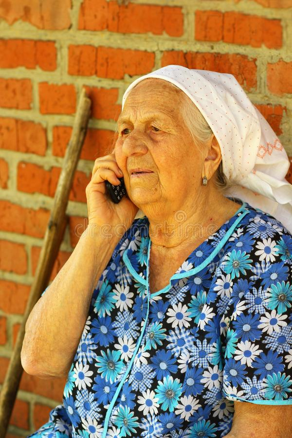 Portrait de dame âgée plus de 90 années parlant au téléphone portable dehors photographie stock