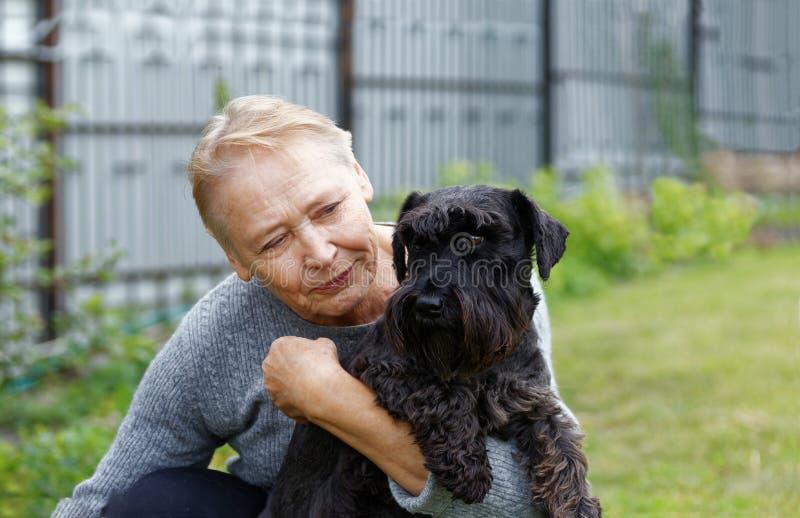 Portrait de dame âgée tenant le chien noir images libres de droits