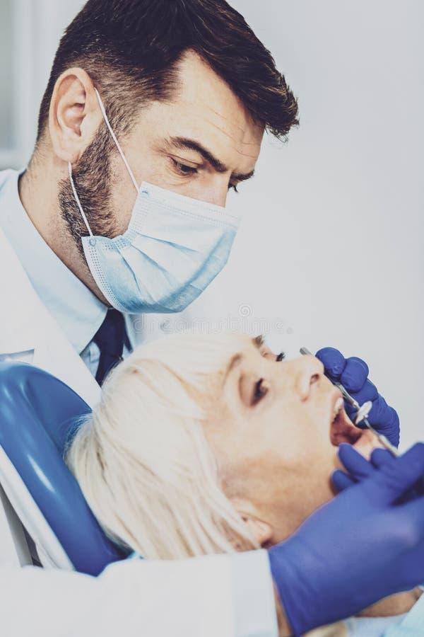 Portrait de dentiste professionnel ce patient de traitement image libre de droits