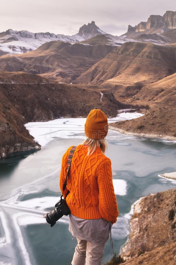 Portrait de derrière du photographe de voyageuse de fille dans un chandail et un chapeau oranges avec une caméra à disposition da photo libre de droits