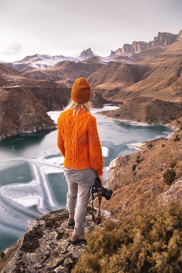 Portrait de derrière du photographe de voyageuse de fille dans un chandail et un chapeau oranges avec une caméra à disposition da photographie stock