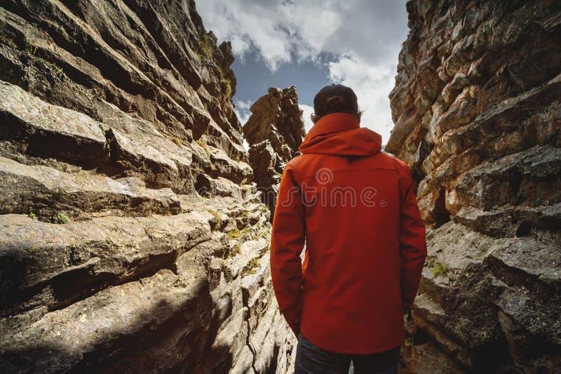 Portrait de derrière de la tondeuse dans une veste de membrane en gorge étroite d'une roche structurelle contre le ciel avec photo libre de droits