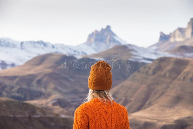 Portrait de derrière de la voyageuse de fille dans un chandail et un chapeau oranges dans les montagnes dans la perspective d'a photos stock