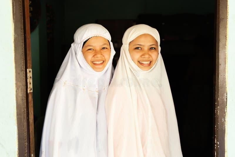 Portrait de deux adolescentes musulmanes de charme dans l'habillement traditionnel souriant à la caméra image stock