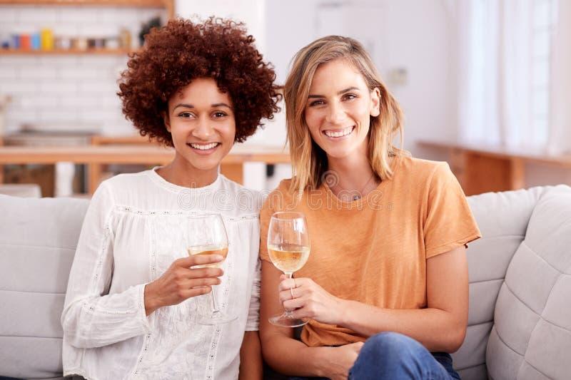 Portrait de deux amis féminins détendant sur Sofa At Home With Glass de vin parlant ensemble photos stock