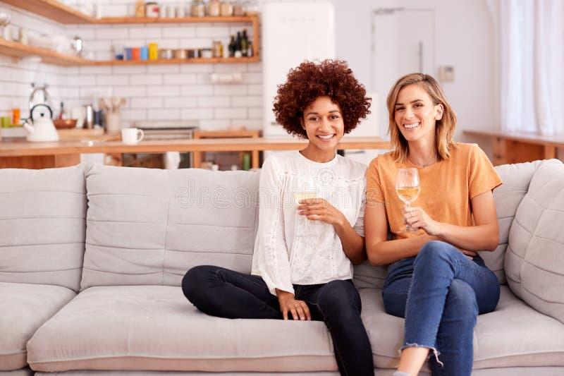 Portrait de deux amis féminins détendant sur Sofa At Home With Glass de vin parlant ensemble image stock