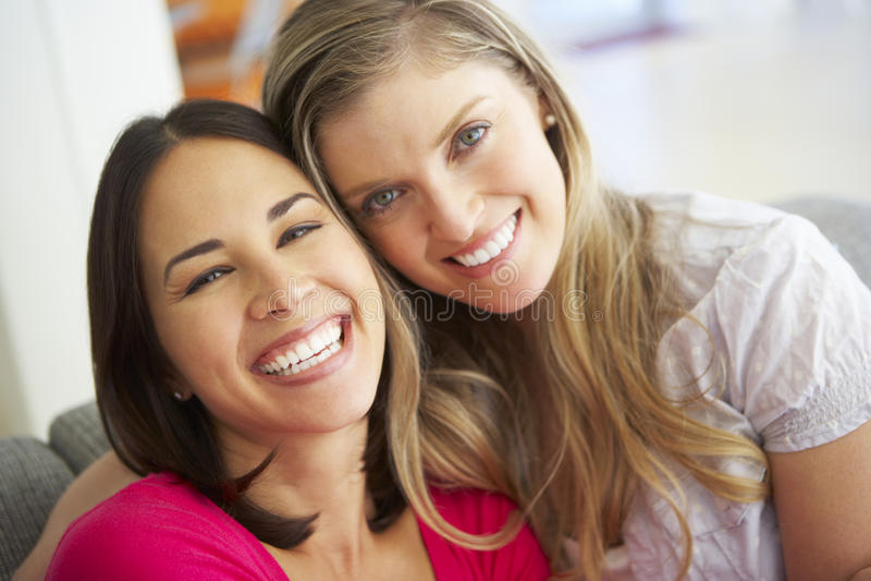 Portrait de deux amis féminins de sourire sur le sofa image stock