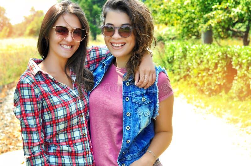 Portrait de deux amis féminins riants utilisant des lunettes de soleil regardant la caméra photographie stock libre de droits