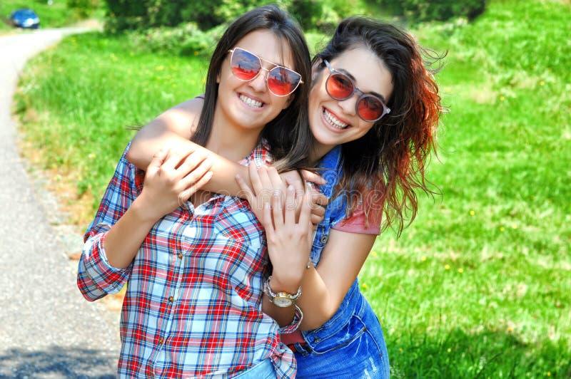 Portrait de deux amis féminins riants utilisant des lunettes de soleil regardant la caméra image stock
