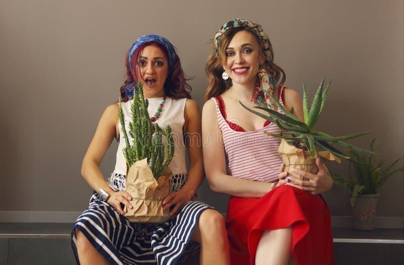 Portrait de deux belles femmes dans l'habillement lumineux et d'arc dans la t?te avec les l?vres lumineuses tenant des cactus photos libres de droits