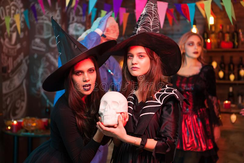 Portrait de deux bons amis habillés comme des sorcières à une partie de Halloween photo stock
