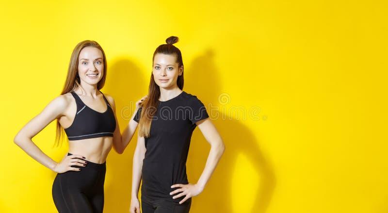 Portrait de deux femelles de forme physique sur le fond jaune Amis de jeunes femmes se tenant contre le mur et le sourire images libres de droits