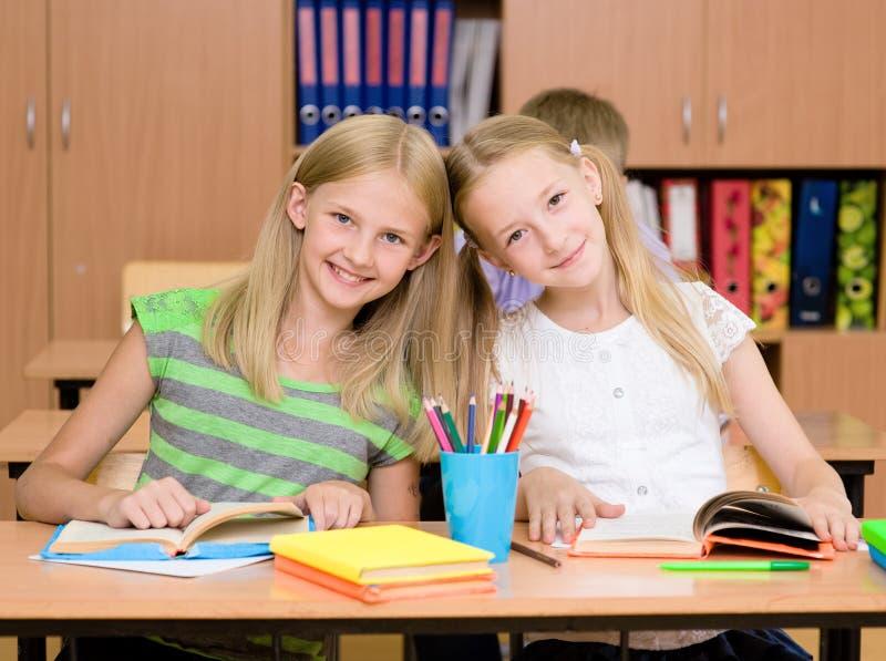 Portrait de deux filles diligentes regardant l'appareil-photo sur le lieu de travail photos stock