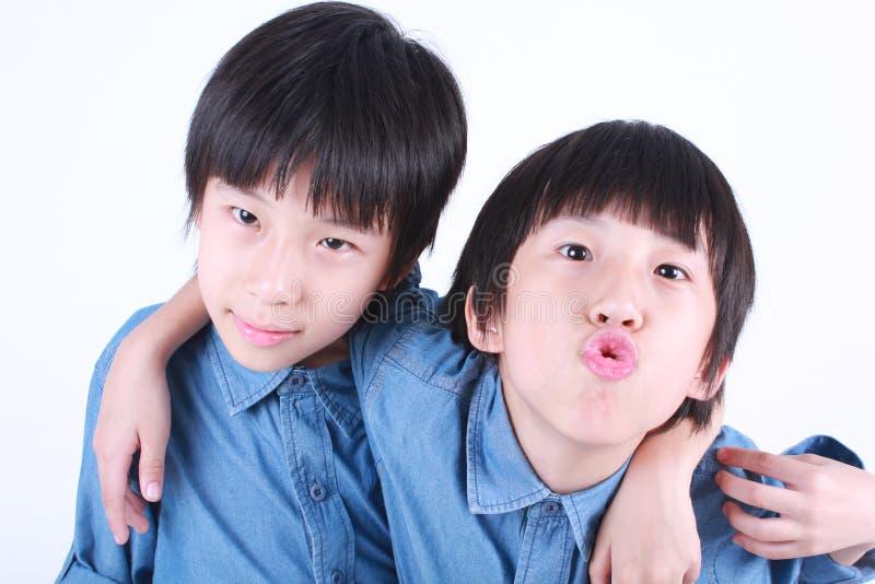 Portrait de deux garçons étreignants, jumeaux images stock