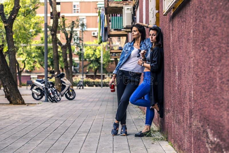 Portrait de deux jeunes et de femmes élégantes se tenant à côté du mur photo stock