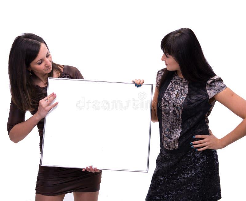 Portrait de deux jeunes femmes avec le panneau-réclame image libre de droits