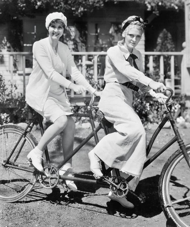 Portrait de deux jeunes femmes s'asseyant sur une bicyclette de tandem (toutes les personnes représentées ne sont pas plus long v photos libres de droits