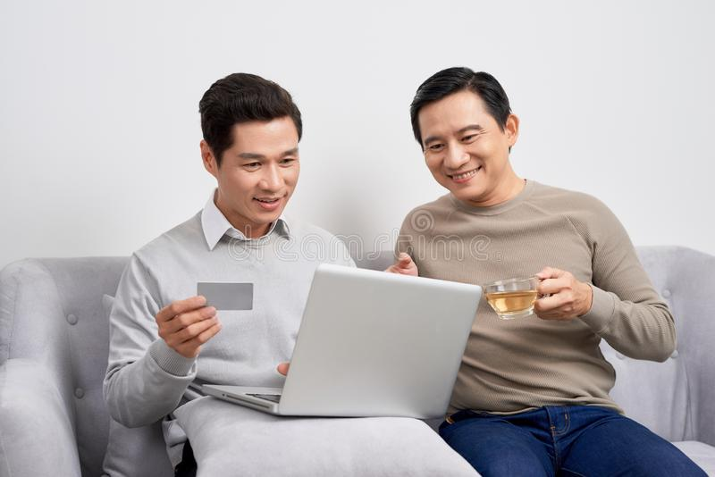 Portrait de deux jeunes hommes enthousiastes tenant l'ordinateur portable tout en dirigeant le doigt à une carte de crédit et cél image libre de droits