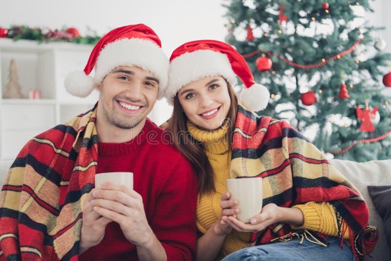 Portrait de deux personnes romantiques en santa claus capes ont romance profiter de Noël atmosphère saint tenir tasse assis sur l photo libre de droits