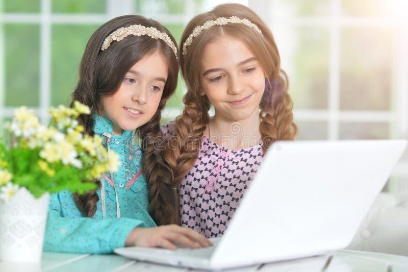 Portrait de deux petites filles mignonnes utilisant l'ordinateur portable ensemble images libres de droits