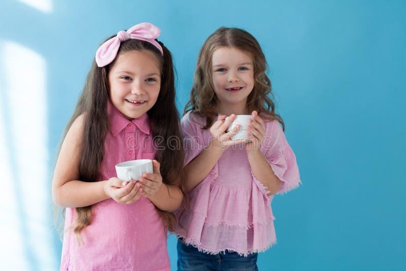 Portrait de deux de petites filles soeurs d'amies sur un fond bleu photo libre de droits