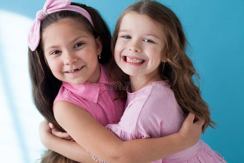 Portrait de deux de petites filles soeurs d'amies sur un fond bleu image stock