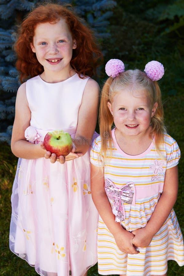 Portrait de deux soeurs mignonnes heureuses dans la robe se tenant sur la pelouse en parc photo libre de droits