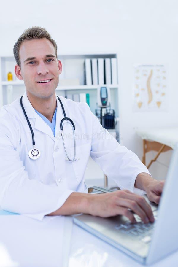 Download Portrait De Docteur De Sourire Travaillant Avec L'ordinateur Portable Image stock - Image du cahier, stéthoscope: 56484185
