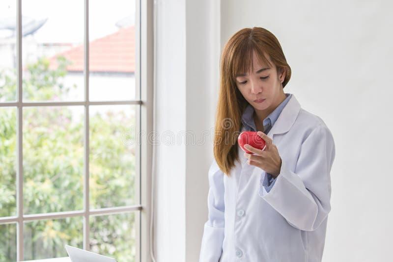 Portrait de docteur féminin de sourire avec le coeur rouge Docteur amical de jeune femme avec le coeur rouge en main l'asie photographie stock