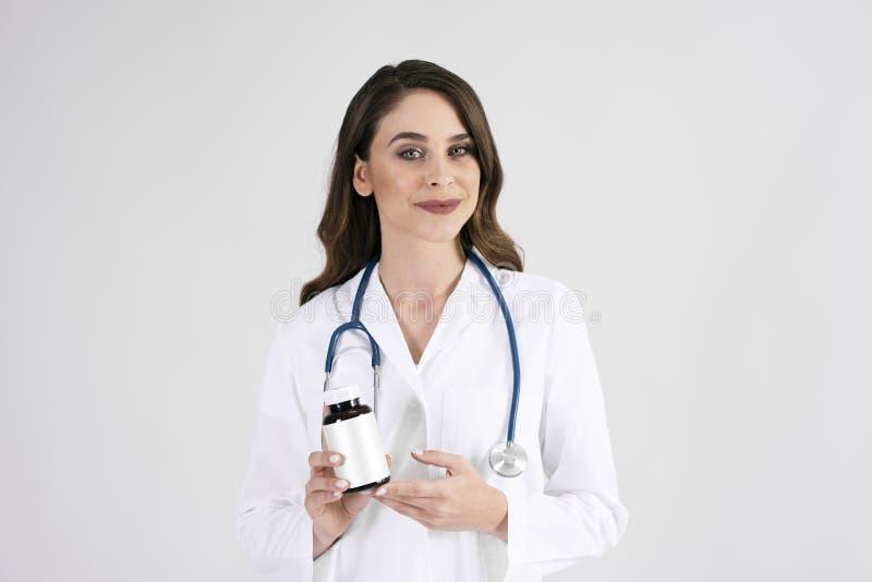 Portrait de docteur féminin de sourire avec le stéthoscope et le médicament image libre de droits