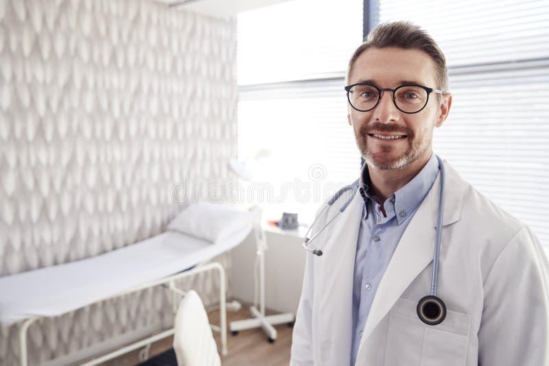 Portrait de docteur masculin mûr de sourire Wearing White Coat avec le stéthoscope se tenant dans le bureau image stock