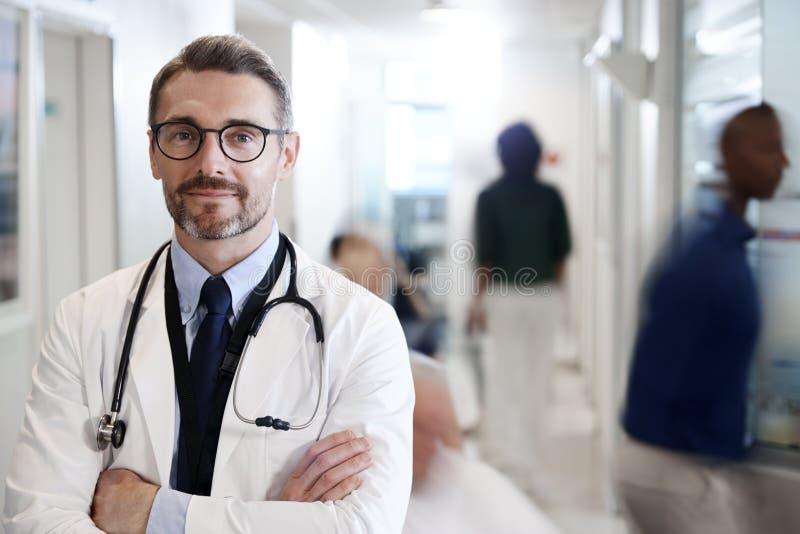 Portrait de docteur masculin mûr Wearing White Coat avec le stéthoscope dans le couloir occupé d'hôpital images stock