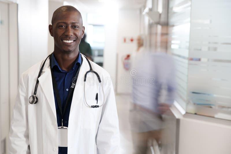 Portrait de docteur masculin de sourire Wearing White Coat avec le stéthoscope dans le couloir occupé d'hôpital images libres de droits