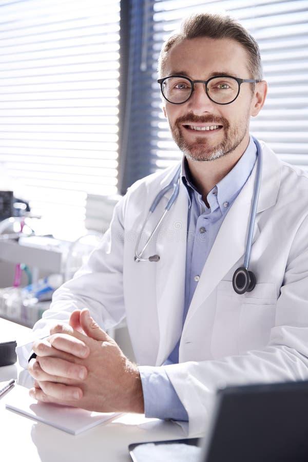 Portrait de docteur masculin de sourire Wearing White Coat avec le stéthoscope se reposant derrière le bureau dans le bureau images stock